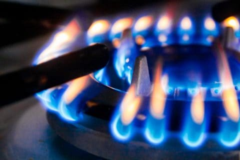 Macro closeup of modern luxury gas stove top with blue fire flame knobs